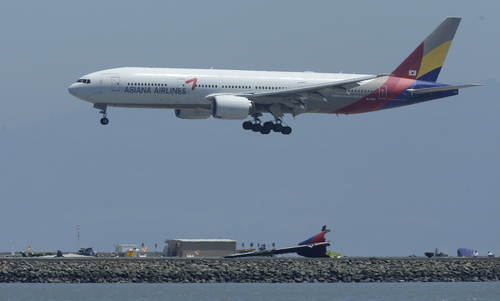 Tuesday's Asiana Flight 214 comes in for a landing over the wreckage of Saturday's Asiana Flight 214 at San Francisco International Airport in San Francisco, Tuesday, July 9, 2013. Saturday's Asiana Flight 214, crashed upon landing, two of the 307 passengers aboard were killed.,  (AP Photo/Jeff Chiu)