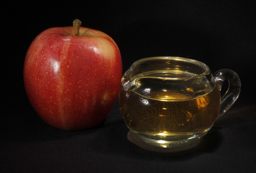 FILE - In this Sept. 15, 2011 photo, an apple and a pitcher of apple juice are posed together in Moreland Hills, Ohio.  The Food and Drug Administration is setting a new limit on the level of arsenic allowed in apple juice, after more than a year of public pressure from consumer groups worried about the contaminant's effects on children. (AP Photo/Amy Sancetta, File)