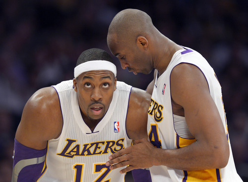 Los Angeles Lakers guard Kobe Bryant, right, chats with center Dwight Howard during the first half of the Lakers' NBA basketball game against the Cleveland Cavaliers, Sunday, Jan. 13, 2013, in Los Angeles. (AP Photo/Mark J. Terrill)