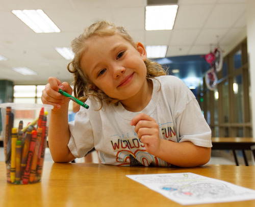 Trent Nelson  |  The Salt Lake Tribune Catie Lloyd coloring pages for welcome kits for faculty and staff at Woodrow Wilson Elementary School in Salt Lake City, Thursday as part of United Way's Summer of Service.