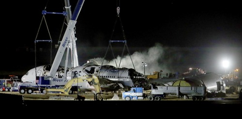 Asiana flight 214 is dismantled and hauled to a hangar at San Francisco International Airport in San Francisco, Calif., on Friday, July 12, 2013. Two people were killed and over 180 injured when the Boeing 777 crashed July 6 as it struck the seawall on the approach to runway 28L, knocking off the plane's tail. (AP Photo/Bay Area News Group, Jane Tyska)