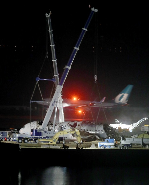 A plane lands at San Francisco International Airport as Asiana flight 214 is dismantled and prepared to be hauled to a hangar in San Francisco, Calif., on Friday, July 12, 2013. Two people were killed and over 180 injured when the Boeing 777 crashed July 6 as it struck the seawall on the approach to runway 28L, knocking off the plane's tail. (AP Photo/Bay Area News Group, Jane Tyska)