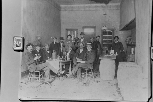 "Salt Lake Tribune archive  A saloon in Mercur around 1895. The town of Mercur, Utah first came into being in 1870 as Lewiston, when gold was discovered at the head of the Lewiston Canyon. A small gold rush began, peaking about 1873. The population reached as high as 2000. Lewiston became a ghost town by 1880 when the ore ran out. In 1890 the gold rush started all over again, and a new town sprang to life on the old site, but the name of Lewiston was already taken by then, so the citizens settled on the name Mercur, In 1902 a fire that started in the business district of the town burned almost the entire city to the ground. The town was rebuilt and mining resumed again. In its heyday, there were about 5,000 residents of Mercur. By 1913 all the mines were closed and by 1916 there was only one building left in Mercur. Mercur supported a large Italian immigrant community. Young men were attracted by the opportunity of high wages and the romance of the American ""wild west."" With this Italian influence, Columbus Day became an important city event including parades, games and performances by the Mercur City Band."
