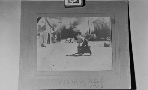 "Salt Lake Tribune archive  A man hauls his belongings from the Prosser house just before it burned in Mercur in 1902. The town of Mercur, Utah first came into being in 1870 as Lewiston, when gold was discovered at the head of the Lewiston Canyon. A small gold rush began, peaking about 1873. The population reached as high as 2000. Lewiston became a ghost town by 1880 when the ore ran out. In 1890 the gold rush started all over again, and a new town sprang to life on the old site, but the name of Lewiston was already taken by then, so the citizens settled on the name Mercur, In 1902 a fire that started in the business district of the town burned almost the entire city to the ground. The town was rebuilt and mining resumed again. In its heyday, there were about 5,000 residents of Mercur. By 1913 all the mines were closed and by 1916 there was only one building left in Mercur. Mercur supported a large Italian immigrant community. Young men were attracted by the opportunity of high wages and the romance of the American ""wild west."" With this Italian influence, Columbus Day became an important city event including parades, games and performances by the Mercur City Band."