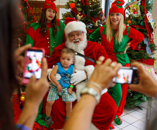 Trent Nelson  |  The Salt Lake Tribune Lyric Padilla poses for a photo with Santa as the Salt Lake Board of Realtors held its annual Christmas in July event at The Road Home homeless shelter in Salt Lake City on Friday, July 12, 2013.