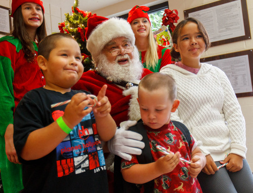 Trent Nelson  |  The Salt Lake Tribune Nikko, Ethan and Felicia Ortega pose for a photo with Santa as the Salt Lake Board of Realtors held its annual Christmas in July event at The Road Home homeless shelter in Salt Lake City on Friday, July 12, 2013.
