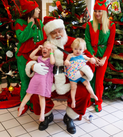 Trent Nelson  |  The Salt Lake Tribune Elliana and Abigail Butterfield pose for a photo with Santa as the Salt Lake Board of Realtors held its annual Christmas in July event at The Road Home homeless shelter in Salt Lake City on Friday, July 12, 2013.