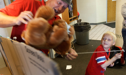 Trent Nelson  |  The Salt Lake Tribune Nathan Stanley snags a stuffed bear in a fishing game run by volunteer Steve Critchfield as the Salt Lake Board of Realtors held its annual Christmas in July event at The Road Home homeless shelter in Salt Lake City on Friday, July 12, 2013.