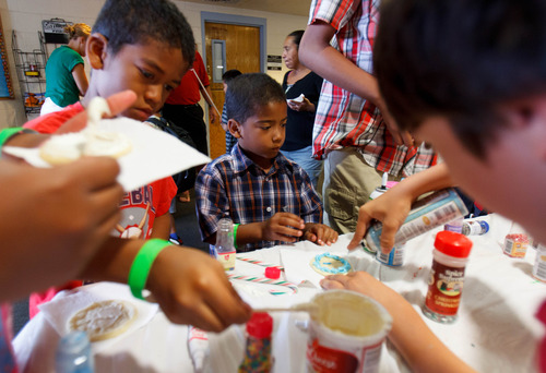 Trent Nelson  |  The Salt Lake Tribune Joseph and Joshua Gaither decorate cookies as the Salt Lake Board of Realtors held its annual Christmas in July event at The Road Home homeless shelter in Salt Lake City on Friday, July 12, 2013.