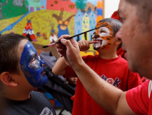 Trent Nelson  |  The Salt Lake Tribune Leo Perez paints Christopher Aguilar's face as his brother Jonathan looks on as the Salt Lake Board of Realtors held its annual Christmas in July event at The Road Home homeless shelter in Salt Lake City on Friday, July 12, 2013.