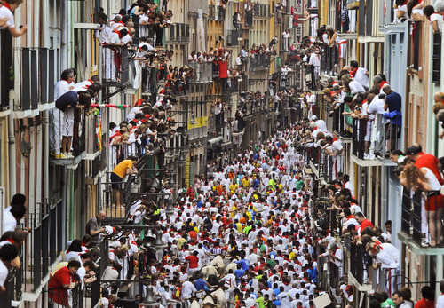 "Runners make their way through the street with ""El Pilar"" fighting bulls watched by people from their balconies during the running of the bulls at the San Fermin festival, in Pamplona, Spain, Friday, July 12, 2013. Revelers from around the world arrive to Pamplona every year to take part in some of the eight days of the running of the bulls glorified by Ernest Hemingway's 1926 novel ""The Sun Also Rises."" (AP Photo/Alvaro Barrientos)"