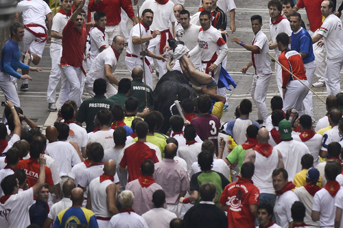 "A runner is gored by an ""El Pilar"" fighting bull during the running of the bulls at the San Fermin festival, in Pamplona, Spain, Friday, July 12, 2013. Revelers from around the world arrive to Pamplona every year to take part in some of the eight days of the running of the bulls glorified by Ernest Hemingway's 1926 novel ""The Sun Also Rises."" (AP Photo/Alvaro Barrientos)"