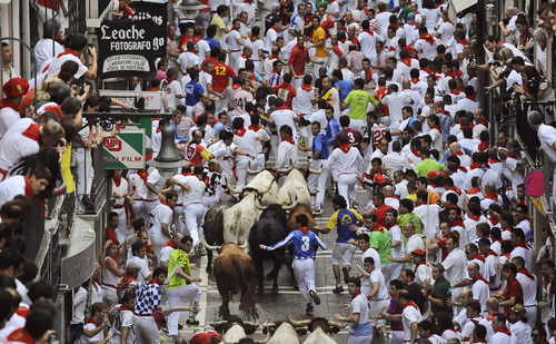"Runners make their way through the street  with ""El Pilar"" fighting bulls watched by people from their balconies during the running of the bulls at the San Fermin festival, in Pamplona, Spain, Friday, July 12, 2013. Revelers from around the world arrive to Pamplona every year to take part in some of the eight days of the running of the bulls. (AP Photo/Alvaro Barrientos)"