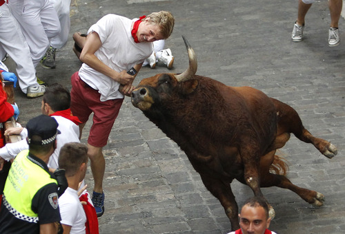 "Patrick Eccles is gored by an ""El Pilar"" fighting bull during the running of the bulls at the San Fermin festival, in Pamplona, Spain, Friday, July 12, 2013. Two Spaniards were also gored Friday during a danger-filled sixth bull run of Spain's San Fermin festival, with one loose bull causing panic in the packed streets of Pamplona city. (AP Photo/STR) SPAIN OUT"