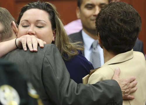 The wife of George Zimmerman, Shellie Zimmerman, left, hugs Robert Zimmerman Sr. and Gladys Zimmerman after Zimmerman's not guilty verdict was read in Seminole Circuit Court in Sanford, Fla. on Saturday, July 13, 2013. Jurors found Zimmerman not guilty of second-degree murder in the fatal shooting of 17-year-old Trayvon Martin in Sanford, Fla. (AP Photo/Gary W. Green, Pool)
