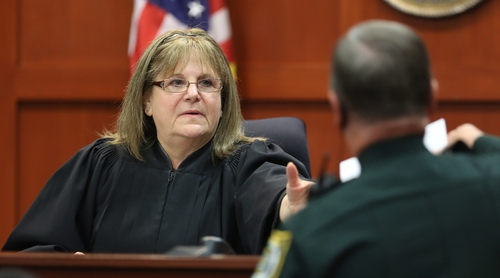 Judge Debra Nelson receives the verdict from a deputy announcing George Zimmerman is not guilty, at the Seminole Circuit Court, in Sanford, Fla., Saturday, July  13, 2013. Neighborhood watch captain George Zimmerman was cleared of all charges Saturday in the shooting of Trayvon Martin, the unarmed black teenager whose killing unleashed furious debate across the U.S. over racial profiling, self-defense and equal justice. (AP Photo/Orlando Sentinel, Joe Burbank, Pool)