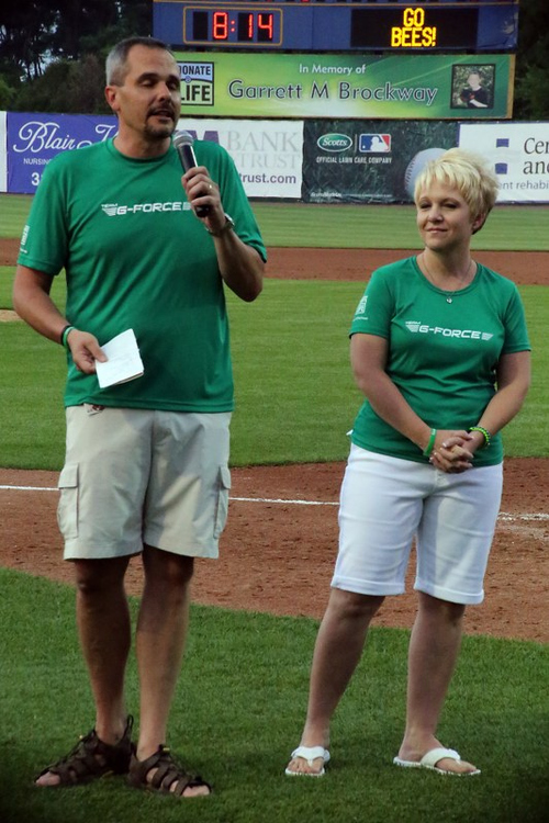 """Photo courtesy Burlington Bees  Bruce and Tiffini Brockway, with a banner of their son Garrett in the background, speak to the crowd on Donate Life Night at the Burlington Bees game in June 2013. Garrett passed away in February 2013 at the age of 10. By donating his organs, Garrett was able to save five lives. In June, the Bees hosted a """"Donate Life"""" night to raise awareness of organ donation and to honor Garrett. He was set to be a batboy this season for the Bees."""