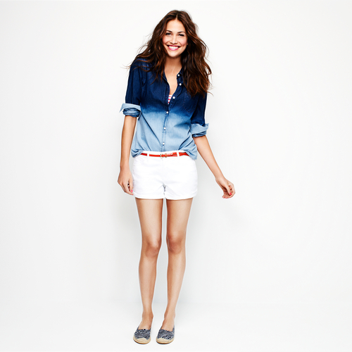 In this product image released by Old Navy, a model wears white denim shorts and a two-tone blue denim top. Many stores are recognizing that shoppers like to purchase their summer clothing when the weather is warm enough for them to wear it. That translates to a later, more gradual rollout of summer clothing as well as staggered and later-than-usual sales. (AP Photo/Old Navy)