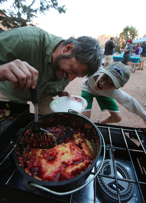 Francisco Kjolseth  |  The Salt Lake Tribune Brett Prettyman is photobombed by his son Will, 11, as he dishes out cherry cobbler from a Dutch oven while camping in Arches National Park.