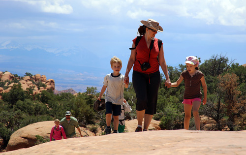 Francisco Kjolseth  |  The Salt Lake Tribune Toni Schmader, center, is joined by her son Hazen Bedke, 4, and Mira Tueller, 5, as they walk the Devils Garden trail in search of arches.