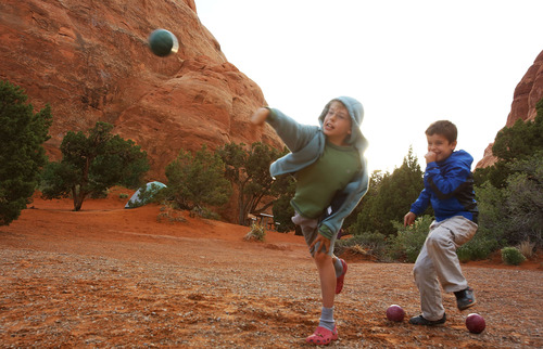 Francisco Kjolseth  |  The Salt Lake Tribune After a long fun-filled day of hiking, bug tracking and making up games, Everett Tueller, 9, left, and Teo Droguett, 8, keep going strong as they play a game of bocce ball while camping in Arches National Park.