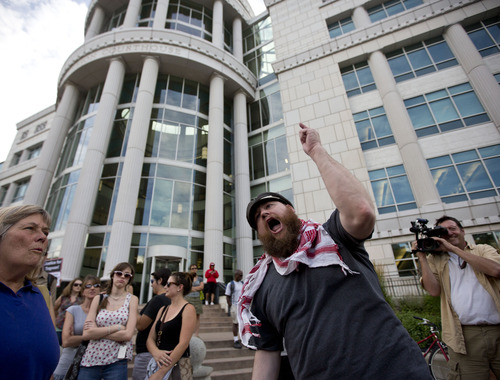 """Lennie Mahler     The Salt Lake Tribune Jacob Jensen leads a chant during a rally to honor Trayvon Martin and condemn the jury which found George Zimmerman not guilty of murder. Jensen asked, """"Who will indict the US justice system for finding George Zimmerman innocent?"""" Salt Lake City, Utah. Monday, July 15, 2013."""