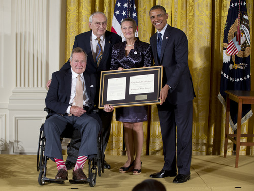 """President Barack Obama with former President George H. W. Bush, presents the 5,000th Daily Point of Light Award to Floyd Hammer and Kathy Hamilton, center, a retired couple and farm owners from Union, Iowa, in the East Room of the White House in Washington, Monday, July 15, 2013. Obama welcomed Bush to the White House in a salute to public service and to the drive for volunteerism that the 41st president inspired with his """"thousand points of light"""" initiative more than two decades ago.  (AP Photo/Carolyn Kaster)"""