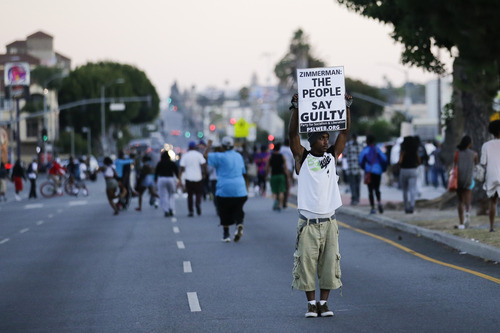 A protester holds up a sign while marching down the street during a demonstration in reaction to the acquittal of neighborhood watch volunteer George Zimmerman on Monday, July 15, 2013, in Los Angeles. Anger over the acquittal of a U.S. neighborhood watch volunteer who shot dead an unarmed black teenager continued Monday, with civil rights leaders saying mostly peaceful protests will continue this weekend with vigils in dozens of cities. (AP Photo/Jae C. Hong)