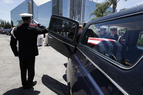 Pallbearers load the casket containing the body of firefighter Kevin Woyjeck back into the hearse after funeral services at Christ Cathedral on Tuesday, July 16, 2013, in Garden Grove, Calif. Woyjeck was among 19 firefighters who were killed while battling an Arizona wildfire on June 30. (AP Photo/Jae C. Hong)