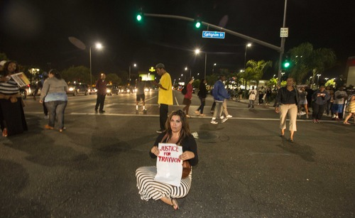 A demonstrator with a sign sits on the intersection of Crenshaw Boulevard and Coliseum street during a protest in Los Angeles on Sunday, July 14, 2013, the day after George Zimmerman was found not guilty in the shooting death of Trayvon Martin. Seventeen-year-old Martin was shot and killed in February 2012 by neighborhood watch volunteer George Zimmerman.  (AP Photo/Ringo H.W. Chiu)