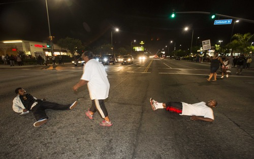 Demonstrators lay on the intersection of Crenshaw Boulevard and Coliseum street during a protest in Los Angeles on Sunday, July 14, 2013, the day after George Zimmerman was found not guilty in the shooting death of Trayvon Martin. Seventeen-year-old Martin was shot and killed in February 2012 by neighborhood watch volunteer George Zimmerman.  (AP Photo/Ringo H.W. Chiu)