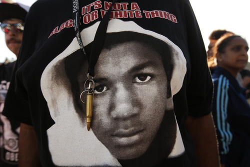 An image of Trayvon Martin and a bullet shell keychain hanging from a protester's lanyard are seen during a demonstration in reaction to the acquittal of neighborhood watch volunteer George Zimmerman on Monday, July 15, 2013, in Los Angeles. Anger over the acquittal of the U.S. neighborhood watch volunteer who shot dead an unarmed black teenager continued Monday, with civil rights leaders saying mostly peaceful protests will continue this weekend with vigils in dozens of cities. (AP Photo/Jae C. Hong)