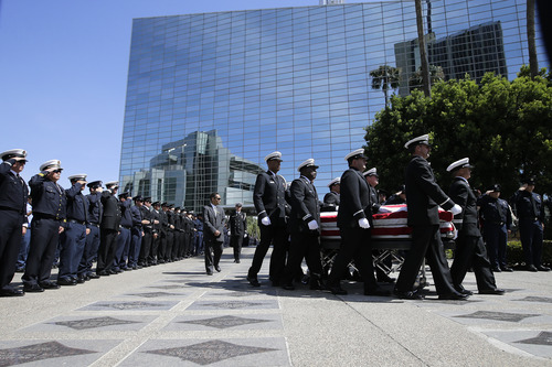 Pallbearers carry the casket containing the body of firefighter Kevin Woyjeck during funeral services at Christ Cathedral on Tuesday, July 16, 2013, in Garden Grove, Calif. Woyjeck was among 19 firefighters who were killed while battling an Arizona wildfire on June 30. (AP Photo/Jae C. Hong)