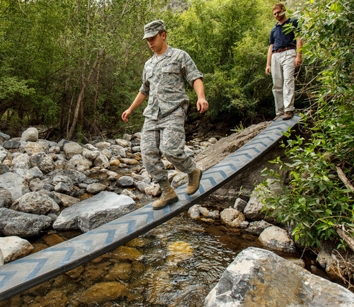 Trent Nelson  |  The Salt Lake Tribune US Air Force ROTC Cadet Jacob Singleton crosses Utah State University's winning design of a Break-Apart Mobile Bridging and Infiltration device (BAMBI) during a demonstration Tuesday July 16, 2013 in Logan Canyon. At right is USU student Benjamin Scott