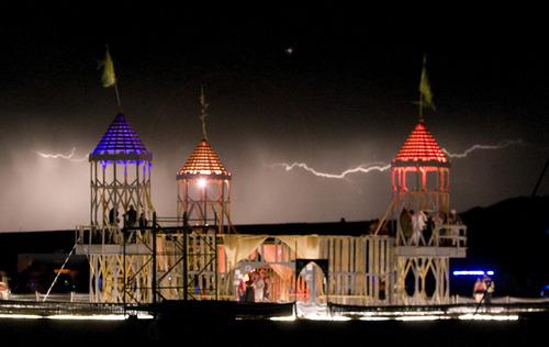 Rick Egan  | The Salt Lake Tribune   Lightning flashes behind the Labyrinth 2013 Castle Effigy at the Element 11 Arts Festival at Bonneville Seabase, Friday, July 12, 2013.