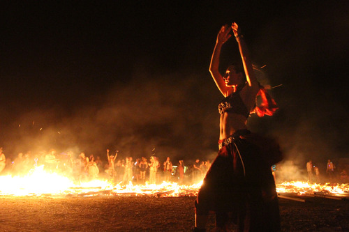 Rick Egan  | The Salt Lake Tribune   Nala Rogers dances around the flames of the Valhalla Viking Ship after it was set on fire late Saturday during the Element 11 Arts Festival at Bonneville Seabase, Saturday, July 13, 2013.