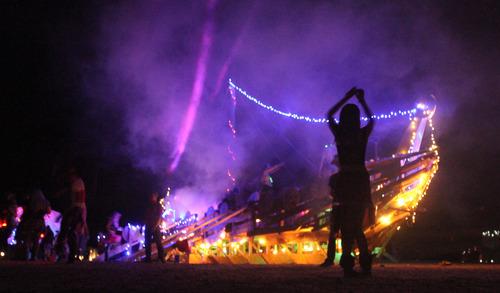 Rick Egan  | The Salt Lake Tribune   Particpants dance in front of the Valhalla Viking Ship at the Element 11 Arts Festival at Bonneville Seabase, Thursday, July 11, 2013.