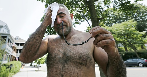 House painter Jesus Rubela wipes the sweat from his face while restoring a home in the South Boston neighborhood, Wednesday, July 17, 2013 in Boston. Temperatures in the Boston area reached the 90's, extending a heat wave. (AP Photo/Charles Krupa)