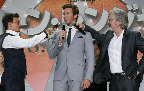 """Actor Johnny Depp, left, and director Gore Verbinski hold microphones up to actor Armie Hammer, center, as he speaks during the Japan premiere of their film """"The Lone Ranger"""" in Tokyo, Wednesday, July 17, 2013. (AP Photo/Shizuo Kambayashi)"""