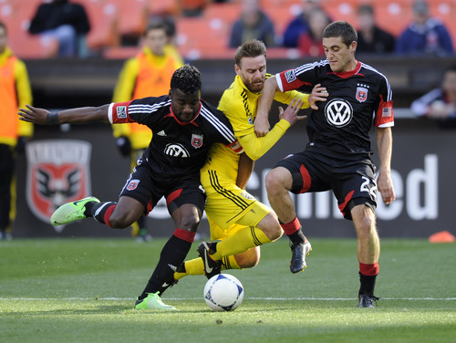 D.C. United defender Brandon McDonald, left, and Chris Korb, right, converge on Columbus Crew midfielder Eddie Gaven, center, during the second half of an MLS soccer game. RSL acquired McDonald on Wednesday, July 17, 2013. (AP Photo/Nick Wass)
