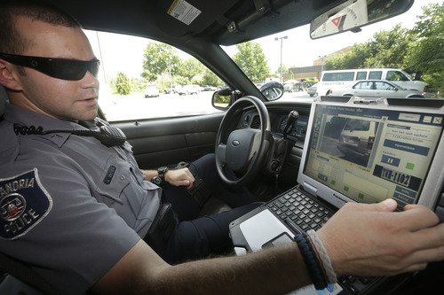 Officer Dennis Vafier, of the Alexandria Police Department, uses a laptop in his squad car to scan vehicle license plates during his patrols, Tuesday, July 16, 2013, in Alexandria, Va. Local police departments across the country have amassed millions of digital records on the location and movements of vehicles with a license plate using automated scanners. Affixed to police cars, bridges or buildings, the scanners capture images of passing or parked vehicles and note their location, dumping that information into police databases. Departments keep the records for weeks or even years. (AP Photo/Pablo Martinez Monsivais)