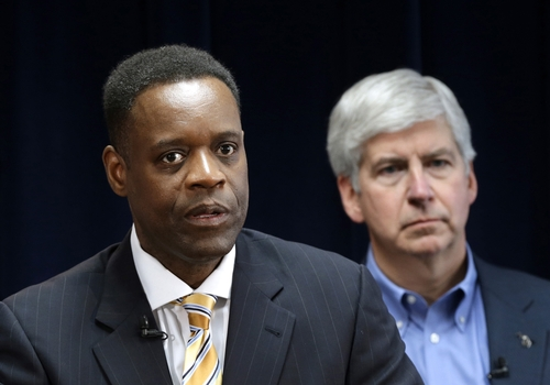 FILE - In this March 14, 2013 file photo Detroit emergency manager Kevyn Orr, left, speaks at a news conference in Detroit as Michigan Gov. Rick Snyder, who appointed Orr, listens. On Thursday, July 18, 2013, Detroit became the largest city in U.S. history to file for bankruptcy when Orr asked a federal judge for municipal bankruptcy protection. (AP Photo/Paul Sancya, File)