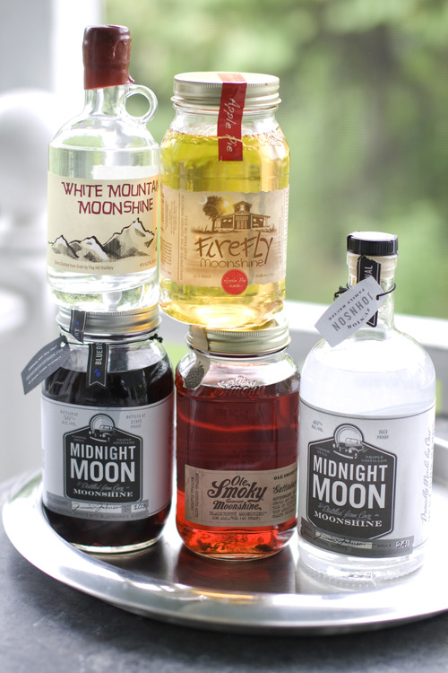 In this image taken on June 10, 2013, from top left clockwise, White Mountain Moonshine, FireFly Moonshine Apple Pie Flavor, Midnight Moon Moonshine, Ole Smoky Tennessee Moonshine Blackberry, and Midnight Moon Blueberry are shown in Concord, N.H. (AP Photo/Matthew Mead)