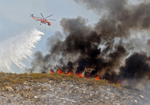 Helicopter crews work the Mountain Fire as it burns in the wilderness near Lake Hemet, Calif. Tuesday, July 17th, 2013. Officials say the wildfire in the mountains west of Palm Springs has destroyed three houses and three mobile homes and is threatening dozens more residences. (AP Photo/The Desert Sun, Jay Calderon)