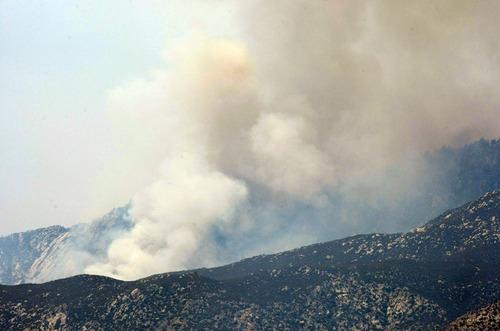 Smoke rises over the ridges above Palm Springs, Calif. as the Mountain Fire advances along the San Jacinto Mountain range, Thursday, July 18, 2013. (AP Photo/The Desert Sun, Michael Snyder)  RIVERSIDE PRESS-ENTERPRISE OUT;  NO SALES; NO FOREIGN