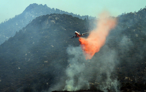 An air tanker fighting the Mountain Fire near Mountain Center drops fire retardant on Tuesday morning, July 16, 2013.  A fast-moving wildfire in the mountains west of Palm Springs nearly doubled in size Tuesday, prompting the evacuation of about 50 homes.   (AP Photo/The Press-Enterprise, Kurt Miller)  NO SALES; MAGS OUT; MANDATORY CREDIT