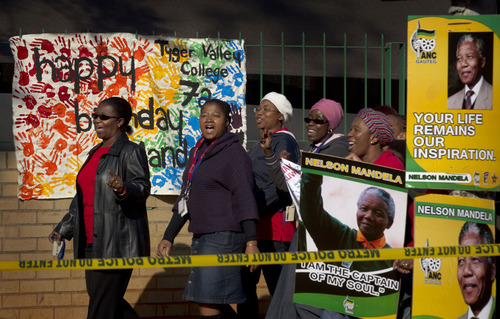 Arriving well-wishers sing as they pass a banner left by schoolchildren wishing Nelson Mandela a happy birthday, outside the Mediclinic Heart Hospital where former South African President Nelson Mandela is being treated in Pretoria, South Africa Thursday, July 18, 2013. South Africa celebrated Nelson Mandela's 95th birthday on Thursday, a milestone capped by news that the former president's health was improving after fears that he was close to death during ongoing hospital treatment. (AP Photo/Ben Curtis)