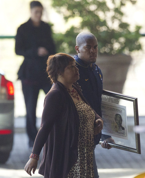 Zindzi Mandela, daughter of former South African President Nelson Mandela, left, accompanied by unidentified man, arrives at the Mediclinic Heart Hospital where Mandela is being treated in Pretoria, South Africa Thursday, July 18, 2013. South Africa celebrated Mandela's 95th birthday on Thursday, a milestone capped by news that the former president's health was improving after fears that he was close to death during ongoing hospital treatment. (AP Photo/Themba Hadebe)