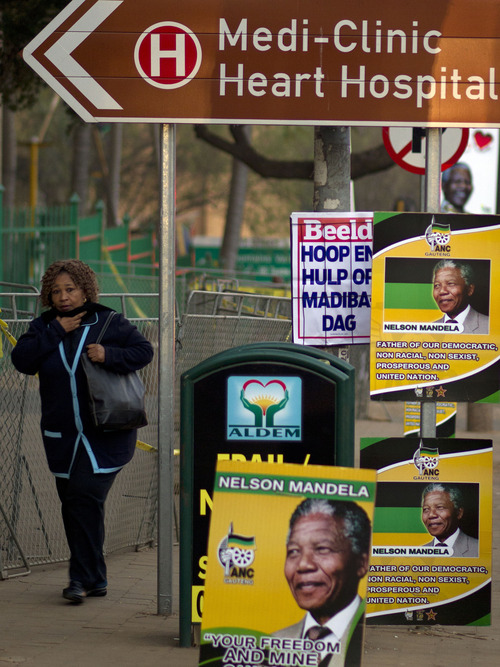 A woman walks past ruling party posters with former South African President Nelson Mandela's face at the Mediclinic Heart Hospital where Mandela is being treated in Pretoria, South Africa Thursday, July 18, 2013. South Africa celebrated Mandela's 95th birthday on Thursday, a milestone capped by news that the former president's health was improving after fears that he was close to death during ongoing hospital treatment. (AP Photo/Themba Hadebe)