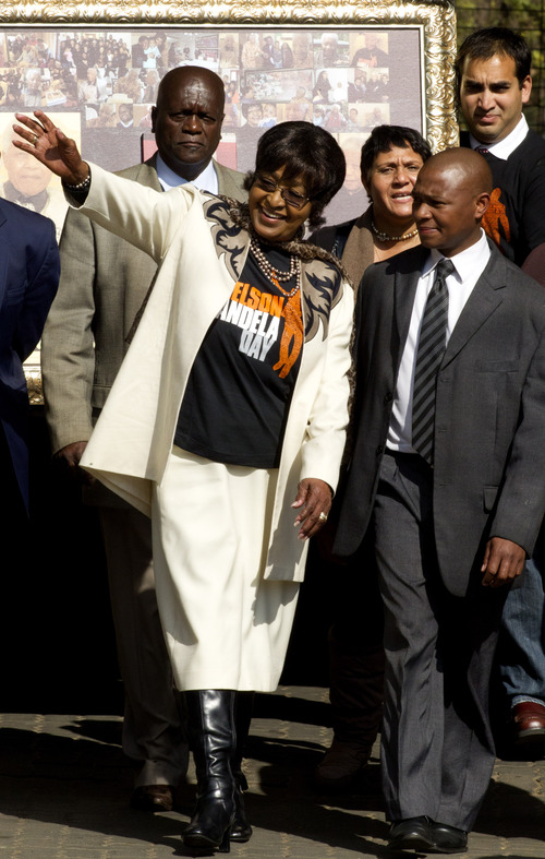 "Former wife Winnie Madikizela-Mandela, left, greets well wishers outside the Mediclinic Heart Hospital where former South African President Nelson Mandela is being treated in Pretoria, South Africa Thursday, July 18, 2013. Mandela will spend his 95th birthday in hospital on Thursday, but was said to be making ""remarkable"" progress. (AP Photo/Themba Hadebe)"